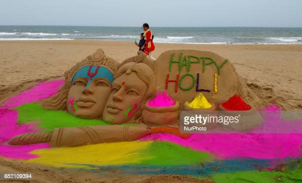 A sand sculpture gives message for the upcoming Holi festival is seen as it creating by sand artist Manas Sahoo at the Bay of Bengal Seas eastern...