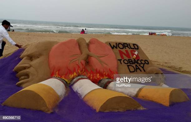 A sand sculpture is seen at the Bay of Bengal Sea's eastern coast beach at Puri to spread awareness on the occasion of World No Tobacco Day 60 km...