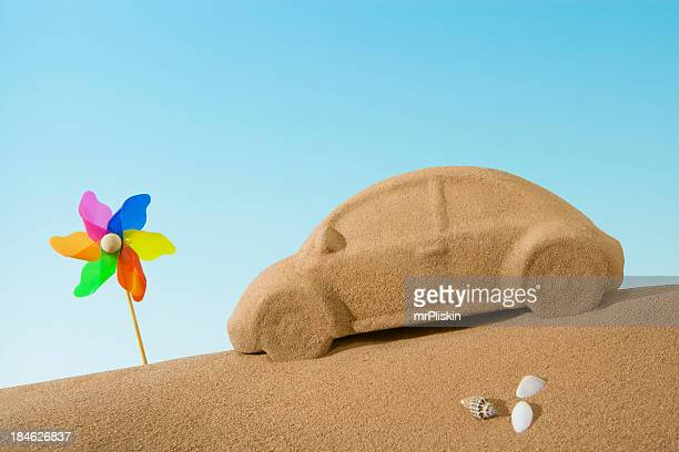 Sand sculpture of car beside toy windmill