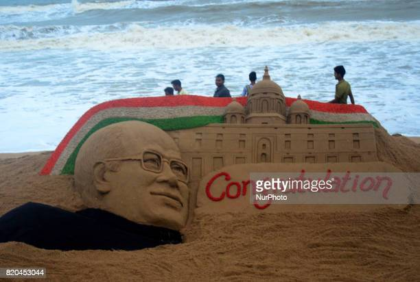 A sand sculpture of newly elected President of India Ramnath Kovind's is seen at the Bay of Bengal Sea's eastern coast beach at Puri as it creates by...