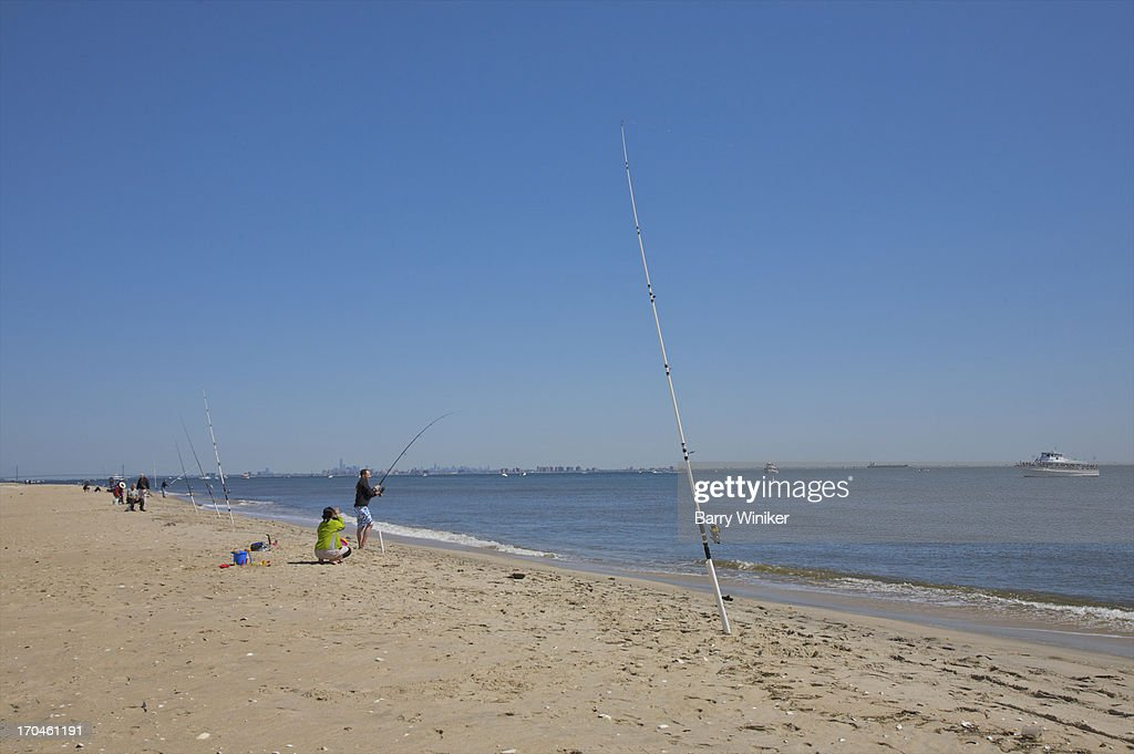Sand, shoreline, water people fishing, blue sky