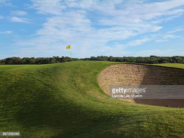 Sand Trap At Golf Course Against Cloudy Sky