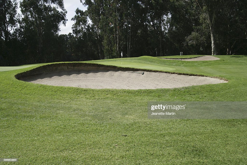 A sand trap in front of a green on a golf course