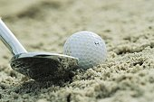 Sand wedge posed next to golf ball on sand