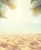 Close up sand with blurred sea sky and plam leaf background, summer day, copy space or for product.