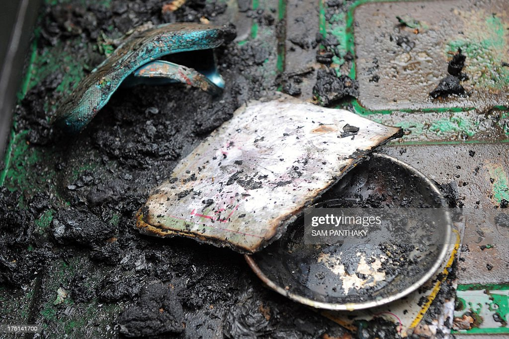 A sandal and a charred school exercise book belonging to one of two girls, who were allegedly set on fire by their father in an auto-rickshaw, are pictured in the vehicle in Ahmedabad on August 1, 2013. Indian auto-rickshaw driver Govindbhai Rathod, a father of four, was arrested for allegedly setting fire to his daughters Neha, 7, and Poonam, 5, as he drove them to school in the vehicle. Police are investigating the incident.