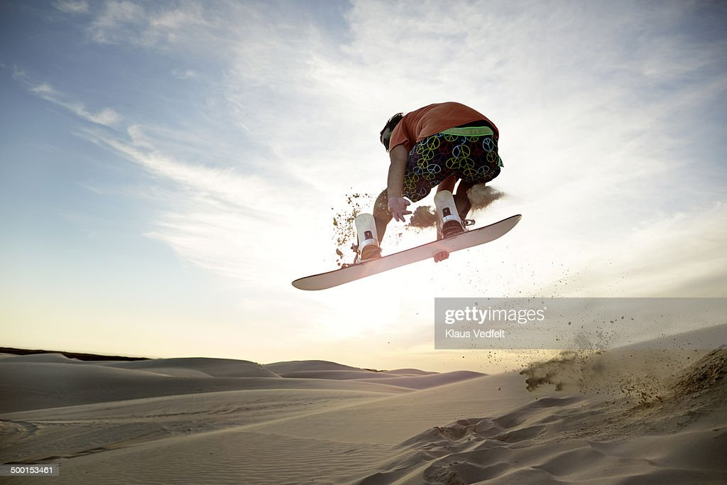 Sandboarder doing front side grab in the air : Stock Photo