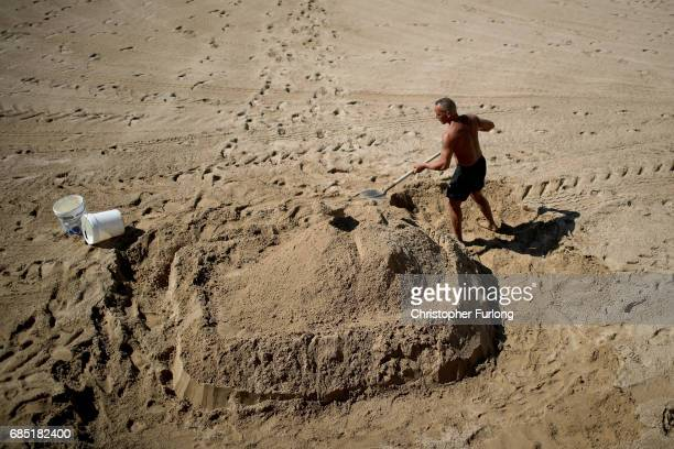 A sandcastle artist builds his foundations on the beach of the Boulevard de la Croisette during the Cannes Film Festival on May 19 2017 in Cannes...