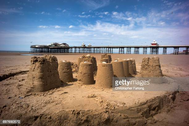 A sandcastle stands in front of Blackpool's North Pier sunshine on June 19 2017 in Blackpool England The UK has officially been put on heatwave alert...
