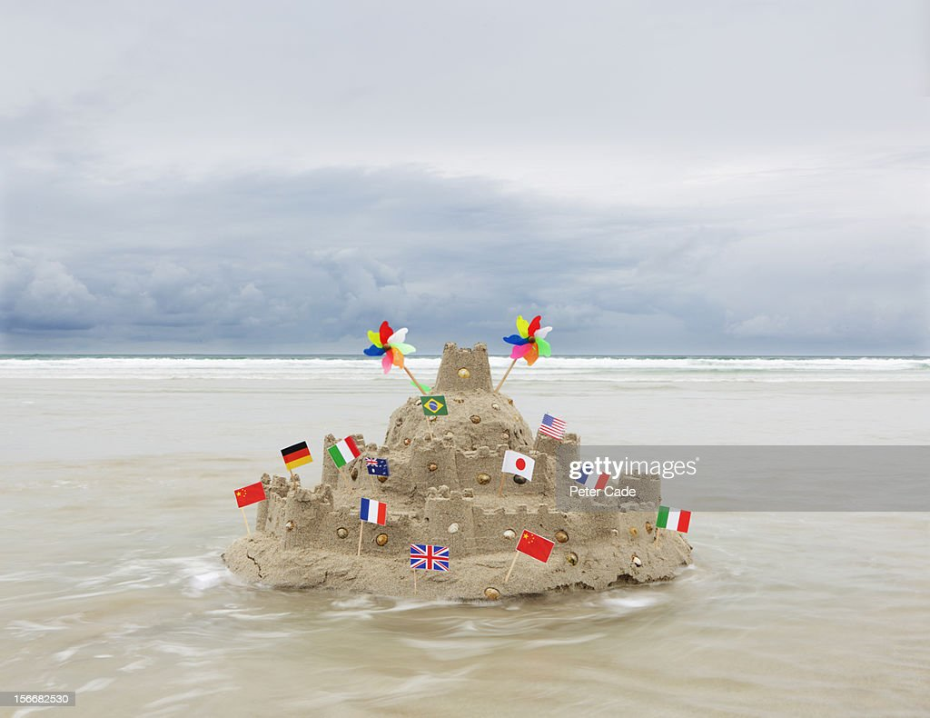 Sandcastle with flags from multiple countries : Stock Photo
