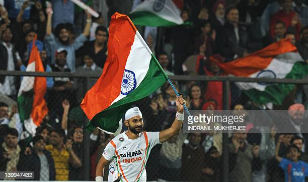 Sandeep Singh of India waves the Indian national flag after winning the men's field hockey finals match between India and France of the FIH London...