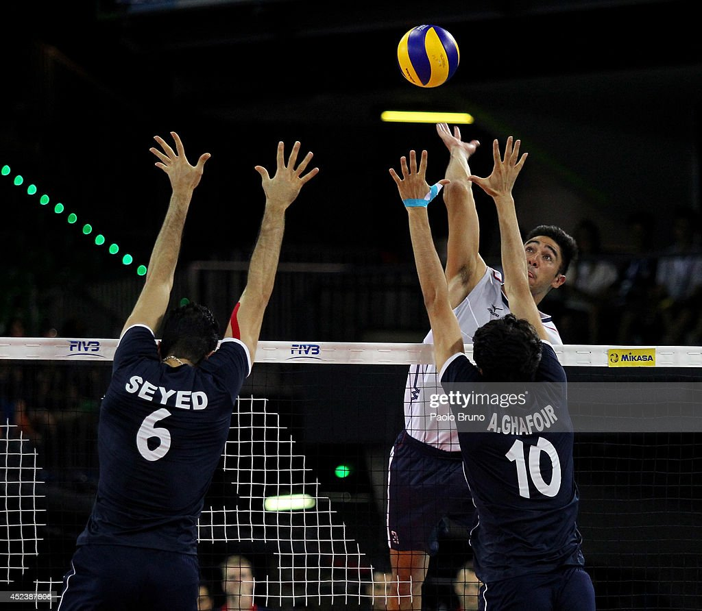 Sander Taylor of United States spikes the ball as Mohammad Seyed and his teammate Ghafour Amir of Iran block during the FIVB World League Final Six semifinal match between Iran and United States at Mandela Forum on July 19, 2014 in Florence, Italy.
