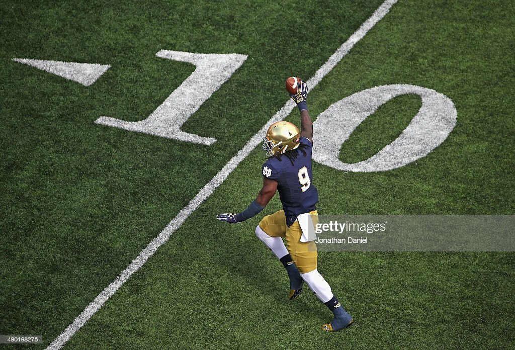 J Sanders of the Notre Dame Fighting Irish holds up the ball as he races towards the end zone against the Massachusetts Minutemen at Notre Dame...