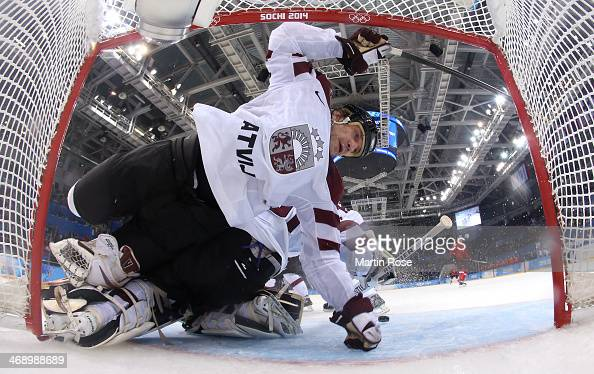 Sandis Ozolins collides with Edgars Masalskis of Latvia in the third period against Switzerland during the Men's Ice Hockey Preliminary Round Group C...