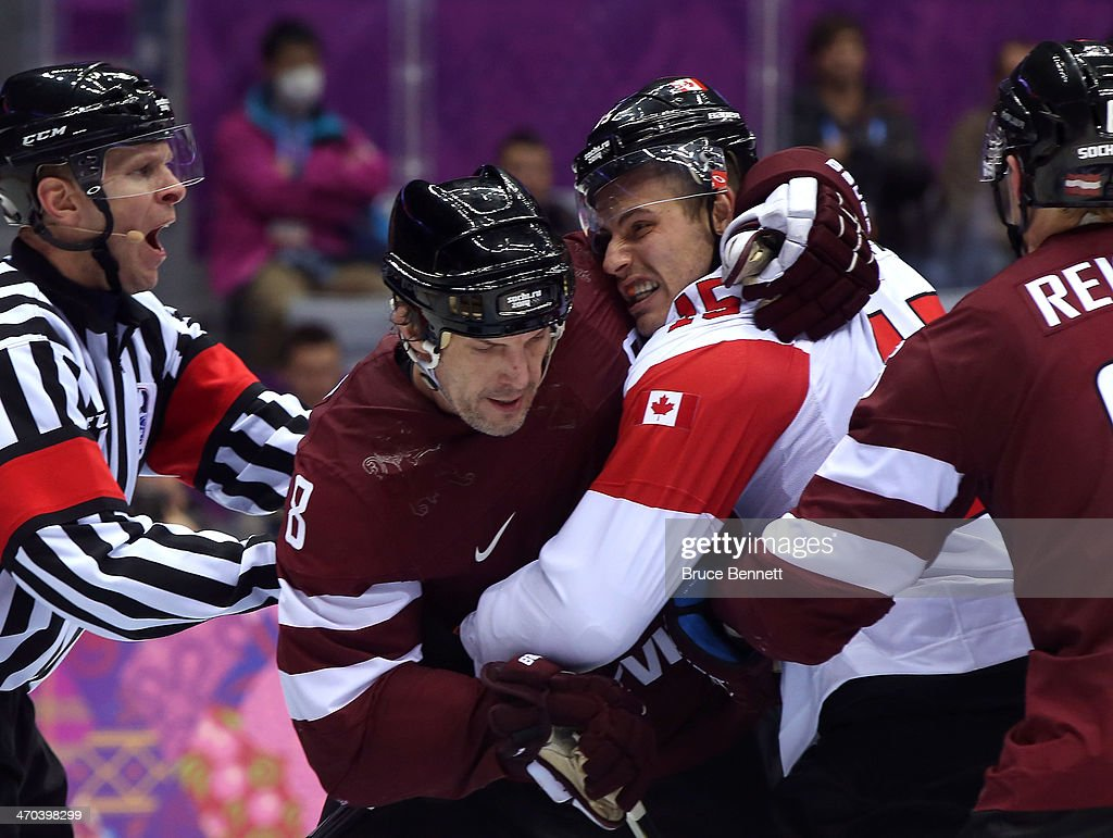 Sandis Ozolins #8 of Latvia and <a gi-track='captionPersonalityLinkClicked' href=/galleries/search?phrase=Ryan+Getzlaf&family=editorial&specificpeople=602655 ng-click='$event.stopPropagation()'>Ryan Getzlaf</a> #15 of Canada shove each other during the Men's Ice Hockey Quarterfinal Playoff on Day 12 of the 2014 Sochi Winter Olympics at Bolshoy Ice Dome on February 19, 2014 in Sochi, Russia.