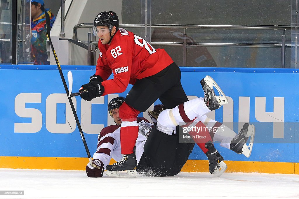 Sandis Ozolins #8 of Latvia hits the ice against <a gi-track='captionPersonalityLinkClicked' href=/galleries/search?phrase=Simon+Moser&family=editorial&specificpeople=7727793 ng-click='$event.stopPropagation()'>Simon Moser</a> #82 of Switzerland in the first period during the Men's Ice Hockey Preliminary Round Group C game on day five of the Sochi 2014 Winter Olympics at Shayba Arena on February 12, 2014 in Sochi, Russia.