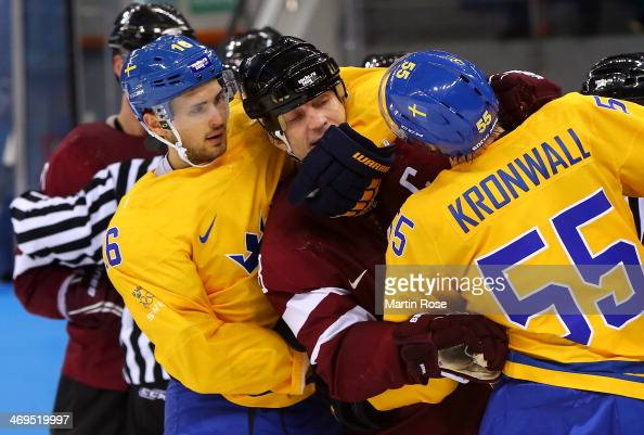 Sandis Ozolins of Latvia pushes Marcus Kruger and Niklas Kronwall of Sweden during an altercation in the third period during the Men's Ice Hockey...