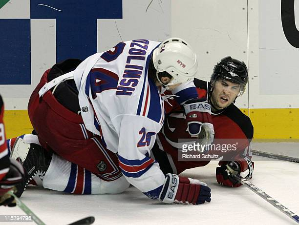 Sandis Ozolinsh of the New York Rangers knocks Brian Gionta of the New Jersey Devils to the ice during the third period of game two in the first...