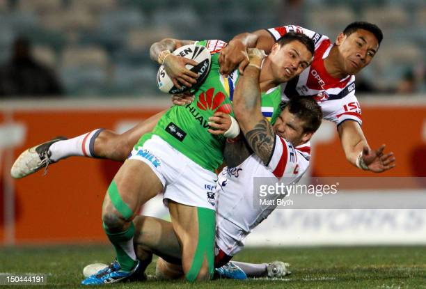 Sandor Earl of the Raiders is tackled during the round 24 NRL match between the Canberra Raiders and the Sydney Roosters at Canberra Stadium on...