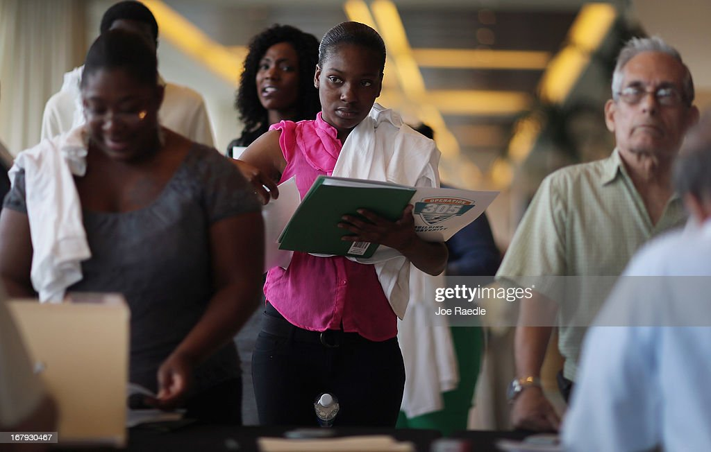 Sandra Bonham (C) and other people looking for work stand in line to apply for jobs during a job fair at the Miami Dolphins Sun Life stadium on May 2, 2013 in Miami, Florida. If voters approve a hotel tax hike to fund stadium renovations the jobs would be available. If not, the Dolphins management is indicating they would not be able to renovate the stadium nor create the jobs.