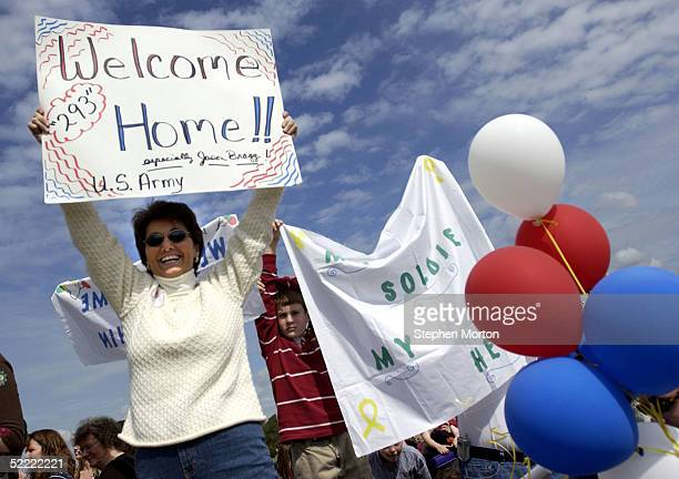 Sandra Bragg holds a sign welcoming her son Spc Jason Bragg as he arrives after a year deployment in Iraq February 20 2005 at Fort Stewart Georgia...
