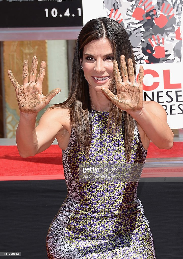 <a gi-track='captionPersonalityLinkClicked' href=/galleries/search?phrase=Sandra+Bullock&family=editorial&specificpeople=202248 ng-click='$event.stopPropagation()'>Sandra Bullock</a> poses for a photo as she is immortalized with a hand and footprint ceremony at TCL Chinese Theatre on September 25, 2013 in Hollywood, California.