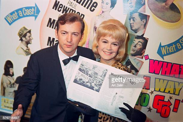 Sandra Dee and Bobby Darin posing in front of a poster for 'What a Way to Go' Hollywood