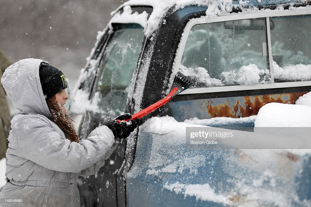 Sandra Duffany works to clear snow from a home on Gay Street in Groton.