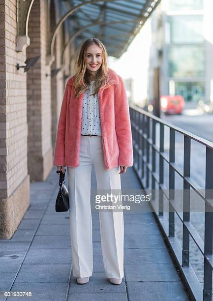 Sandra Kleine Staarman wearing a salmon pink Marc Cain faux fur jacket white wide leg Marc Cain pants and Marc Cain blouse with bow tie black Marc...