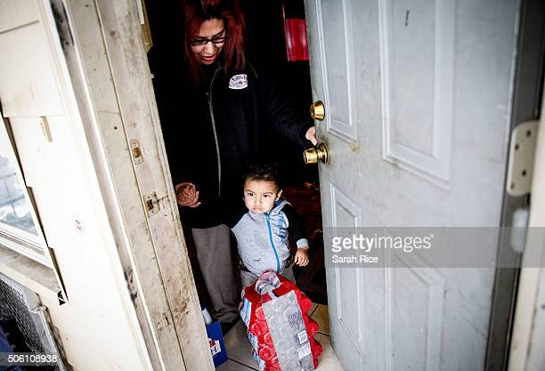 Sandra Mendez and her son Alonzo Cabrera receive water from Red Cross volunteers at their home January 21 2016 in Flint Michigan Mendez said she had...