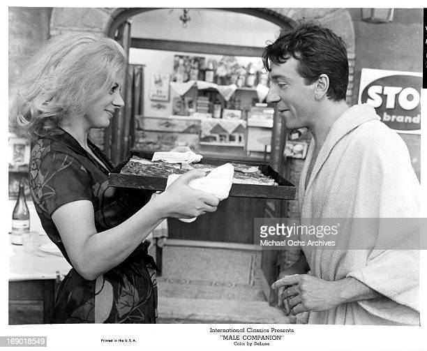 Sandra Milo extending kindness to JeanPierre Cassel with her tray of goods in a scene from the film 'Male Companion' 1964
