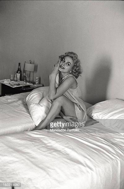 Sandra Milo is seated on a bed in a hotel room and she poses in a blouse showing her legs Venice 1956