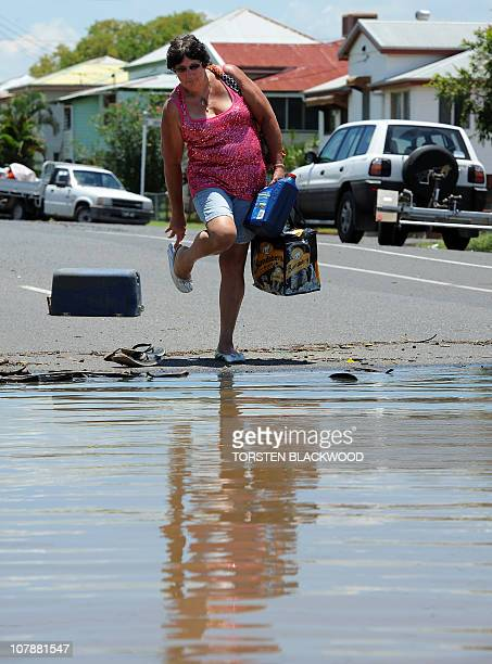 Sandra Shambrook removes her footwear before entering the murky flood waters after the Fitzroy River broke its banks and inundated much of...