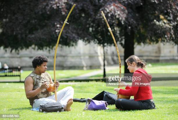 Sandro Alves and Helene Lecomte play the berimbaus a musical instrument used to accompany Brazilian martial arts during the sunny bank holiday...