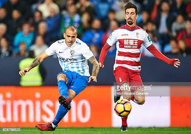 Sandro Ramirez of Malaga CF shoots while is being followed by Isaac Cuenca of Granada CF during La Liga match between Malaga CF and Granada CF at La...