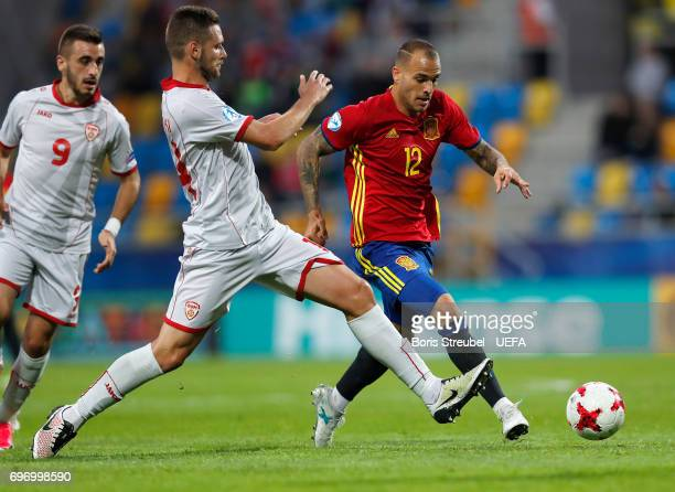 Sandro Ramirez of Spain is challenged by Darko Velkoski of FYR Macedonia during the UEFA European Under21 Championship match between Spain and...