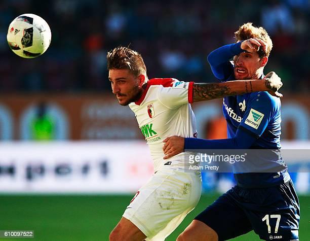 Sandro Sirigu of SV Darmstadt 98 challenges Kostas Stafylidis of Augsburg during the Bundesliga match between FC Augsburg and SV Darmstadt 98 at WWK...