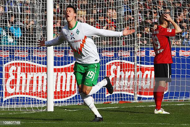 Sandro Wagner of Bremen celebrates his team's first goal as Erik Jendrisek of Freiburg reacts during the Bundesliga match between SC Freiburg and SV...