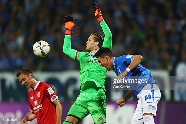 Sandro Wagner of Darmstadt is challenged by goalkeeper Lorius Karius and Niko Bungert of Mainz during the Bundesliga match between SV Darmstadt 98...