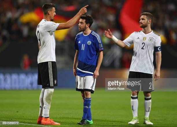 Sandro Wagner of Germany and Tommaso Zafferani of San Marino exchange words as Shkodran Mustafi of Germany looks on during the FIFA 2018 World Cup...