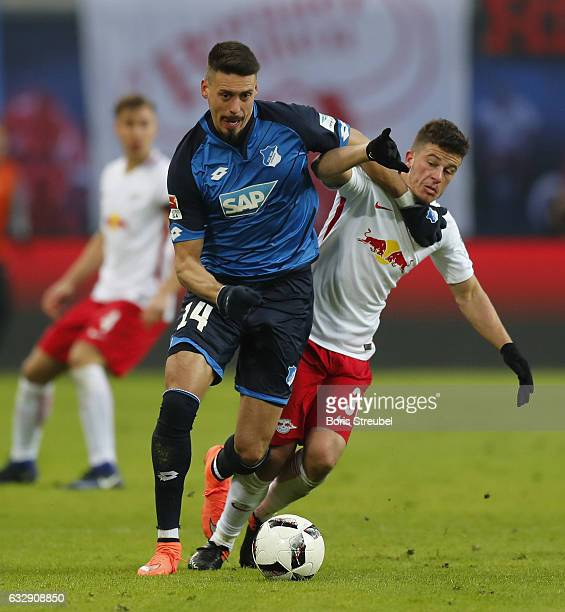Sandro Wagner of TSG Hoffenheim is challenged by Diego Demme of RB Leipzig during the Bundesliga match between RB Leipzig and TSG 1899 Hoffenheim at...
