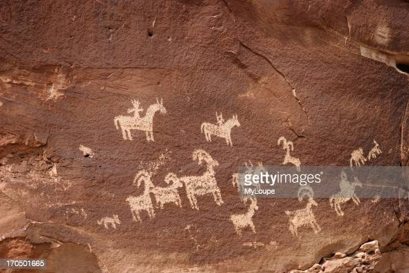 Sandstone Wall With Ancient Indian Writing Or Petroglyphs Showing Horses Dogs Ram And Hunting Scene Southern Utah