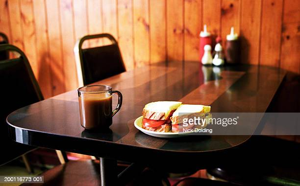 Sandwich and hot drink at edge of cafe table