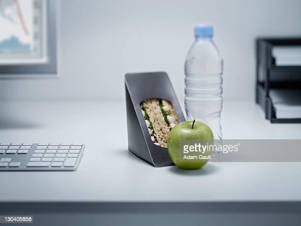 Sandwich, apple and water on office desk