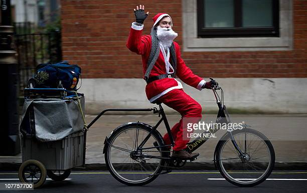 A sandwich delivery courier dressed as Father Christmas waves as he cycles through central London on December 22 2010 AFP PHOTO / LEON NEAL