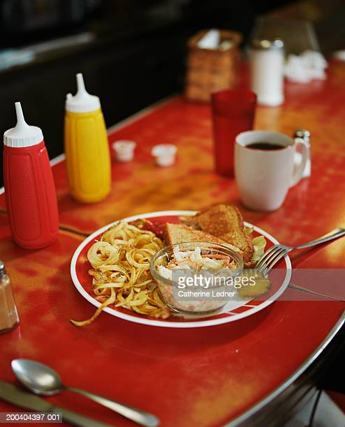 Sandwich, salad and curly fries on plate in diner