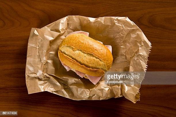 A sandwich sitting on a brown paper bag