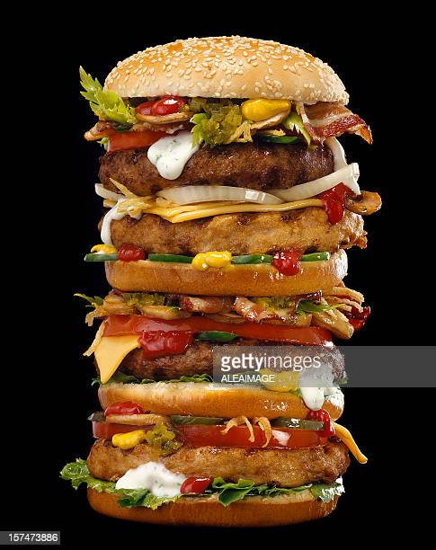 Sandwich stacked high with patties, buns, and many toppings