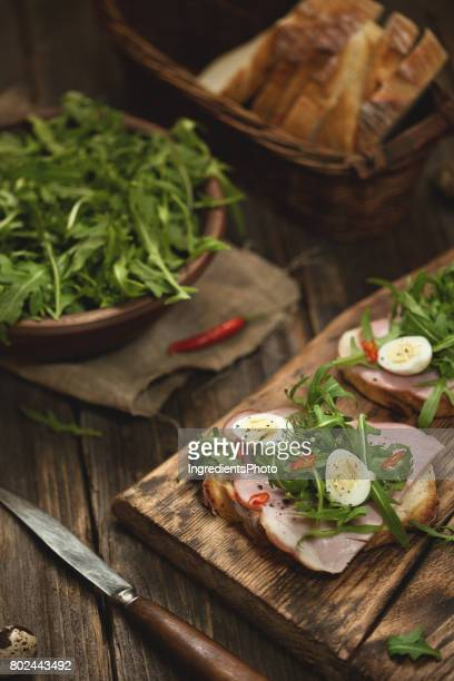 Sandwich with ham and ruccola on a wooden table.