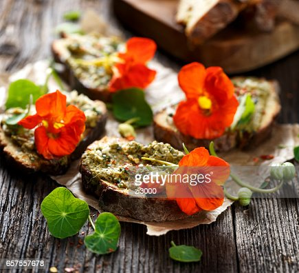 Sandwich with herb pesto and edible nasturtium flowers : Stock Photo